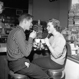Teen Couple on Stools at Soda Fountain Drinking Shakes and Smiling at Each Other