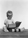 Baby Boy is Wearing Round Glasses While Reading a Very Large Book