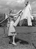 Woman  Housewife  is Outdoors  Hanging Clean Fresh Laundry on Clothesline
