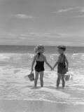 Boy and Girl Standing on Beach  Holding Hands  Rear View