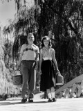 Teenage Couple Walking Across Wooden Bridge Carrying Picnic Basket and Flask