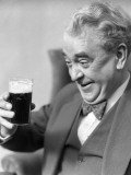 Elderly Man Holding and Staring at a Glass of Beer  Smiling and Laughing With a Happy Expression
