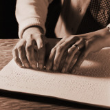 Woman&#39;s Hands Reading Braille