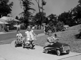 Boy and Two Girls on Suburban Sidewalk  Riding Tricycle and Toy Cars