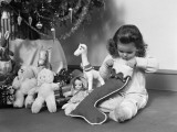 Young Girl in Pajamas  Opening Christmas Stocking Next To Christmas Tree