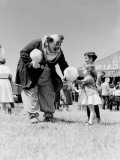 Clown Handing Cotton Candy To Children Outside Circus Tent