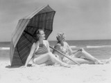 Two Women Sitting on Beach Under Parasol
