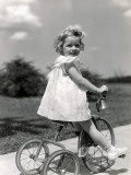 Girl Wearing Summer Dress  Riding Tricycle Down Sidewalk