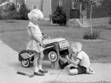 Children on Suburban Sidewalk  Boy Playing As Mechanic  Oiling Toy Pedal Car