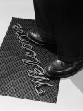 Man Stepping Onto Welcome Mat