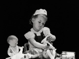 Girl Wearing Nurse&#39;s Cap  Putting Bandages on Doll&#39;s Head