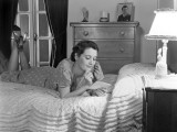 Woman Lying on Bed Reading Letter
