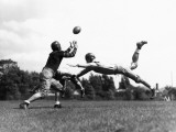 American Football Players Tackling Football in Mid-Air