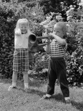 Boy Playing Trumpet in Backyard  Girl Grimacing  Holding Hands Over Her Ears
