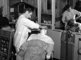 Uniformed Barber Shaving His Customer in the Barber Chair