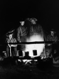 Four Men Wearing Plaid Shirts  Suspenders and Hats  Cooking Over Campfire