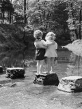 Boy and Girl Standing on Rock Path in Stream  With Arms Around Each Other