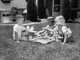 Three Small Children Playing on Front Lawn  Enjoying Picnic on Checkered Tablecloth