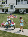 Little Girl With Bugle Leading Girl on Tricycle