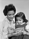 Afro-American Mother and Daughter Looking Down Reading Book Together