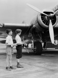 Two Boys Standing Next To Propeller Aeroplane  Holding Toy Plane