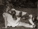 Girl Sitting Outside on Grass  Squinting While a Cocker Spaniel is Licking Her Face