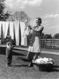 Mother and Daughter Doing Laundry  Hanging Wash on Clothesline in Backyard