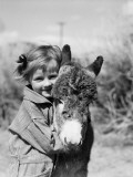 Girl Wearing Striped Overalls  Hugging Burro Donkey