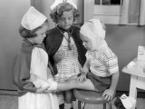 Two Young Girls Dressed As Nurses  Bandaging Three Year Old Boy's Head and Foot