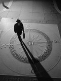 Silhouetted Businessman With Briefcase Walking Across Compass in the Sidewalk