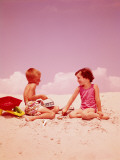 Young Couple Sitting in Sand  By Seashore  Flirting
