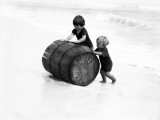Two Boys Rolling Broken Barrel Out of Surf Up Onto Sand Beach  New Jersey