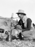 Cowboy Kneeling By Campfire Pouring Coffee