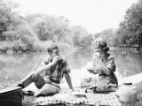 Couple Seated on Checkered Tablecloth With Picnic Basket and Cooler  Eating Sandwiches By Lake