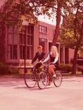 Teenage Couple Riding Bicycles Past High School Buildings
