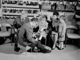 Family in Shoe Shop  Salesman Fitting Shoe on Girl As Mother  Father and Sister Look On