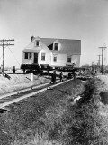 Group of Men Moving House on Wheels Across Railroad Tracks