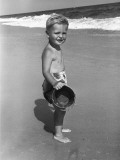 Portrait of Boy (4-5) at Seashore With Bucket