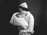 Nurse Hugging Newborn (0-3 Months) Wrapped in Blanket