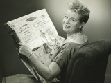 Woman Sitting in Armchair  Reading Newspaper  Smiling