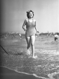 Woman in Swimsuit Running on Shoreline