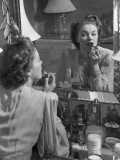 Woman Applying Lip-Stick in Front of Mirror