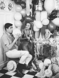 Couple Blowing Up Balloons in Kitchen For Party
