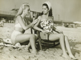 Two Women on Beach Applying Suntan Lotion