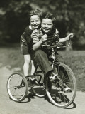 Two Young Boys (6-7) Riding Tricycle in Park  Portrait