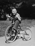 Young Boy (6-7) Riding Tricycle in Park  Portrait