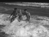 Two Young Man and Woman Playing in Wave