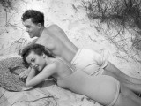 Young Couple in Bathing Suits Lying on Sand