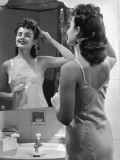Woman Fixing Hair in Mirror