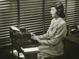 Secretary Typing on Typewriter in Office